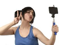 donna-sexy-che-prende-la-foto-del-selfie-con-la-posa-della-macchina-fotografica-del-telefono-cellulare-e-del-bastone-felice-87518619