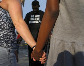 A group holds hands and prays outside the Emanuel African Methodist Episcopal Church in Charleston