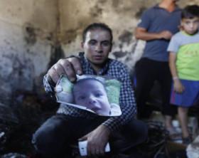 Un-parente-mostra-la-foto-del-piccolo-Ali-ucciso-nel-rogo-della-sua-casa-appiccato-da-coloni-israeliani