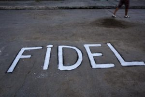 A woman walks by a the word 'Fidel' written on the asphalt near the route made by the motorcade carrying Fidel Castro's ashes to the the Santa Ifigenia cemetery in Santiago, Cuba Sunday, Dec. 4, 2016. Thousands of people lined the short route from the Plaza Antonio Maceo or Plaza of the Revolution to the cemetery where the ashes will be buried in a private ceremony near the grave of Cuba's independence hero Jose Marti. (ANSA/AP Photo/Rodrigo Abd) [CopyrightNotice: Copyright 2016 The Associated Press. All rights reserved.]