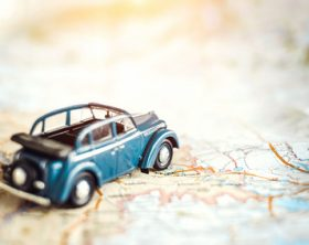 Toy retro cabrio car on the map, tourism concept
