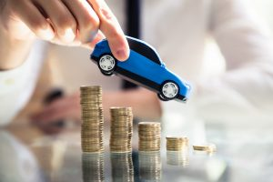 Person Flying Car Over Declining Stacked Coins