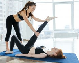 Happy pretty young woman stretching legs with personal trainer