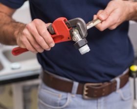 Plumber fixing pipe with wrench in the kitchen